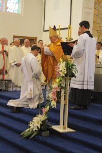 Bishop Meeking lays hands on Fr Blackburn.